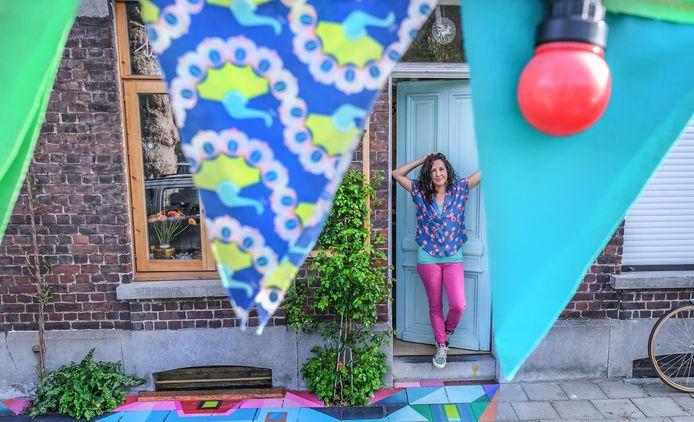 Mónica bij haar voordeur. Onderaan de felle geometrische figuren op de stoep. Op de voorgrond de vlagjes en feestverlichting.