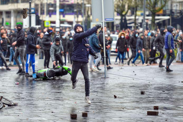 Een relschopper gooit een steen naar de politie op het 18 Septemberplein in Eindhoven. Ook met golfballen, vuurwerk, fietsen en messen werd gegooid.