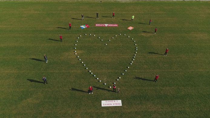 Jong Ambon vormde een groot hart met ballen op het voetbalveld. Daarbij de tekst: samen 1, samen sterk in twee talen.