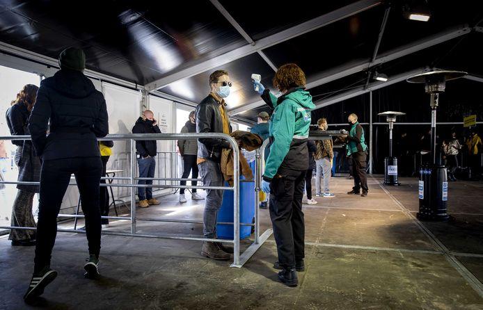 Bezoekers van het dancefestival laten bij binnenkomst hun temperatuur opmeten.