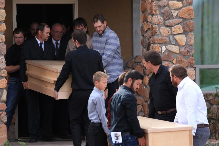 De kisten van twee van de slachtoffers worden weggedragen.