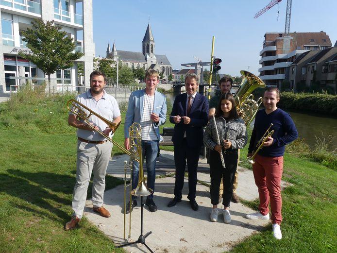 De eerste jeugddirigent van Deinze Sam Stroobandt krijgt de dirigeerstok uit handen van burgemeester Jan Vermeulen (CD&V). Met cultuurschepen Rutger De Reu, muzikanten Bram Stroobandt en Sari Van Welden en dirigent Kenny Van Heuverswijn.