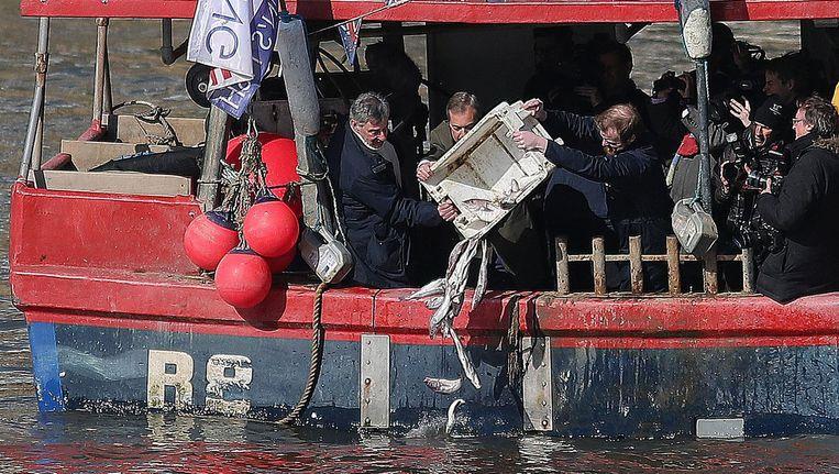 Nigel Farage gooit dode vis in de Theems. Beeld afp