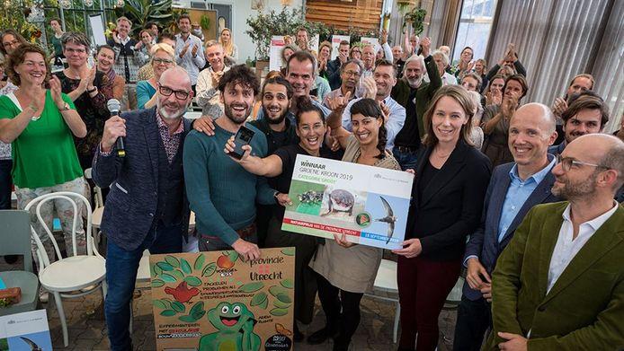 Gedeputeerde Hanke Bruins Slot overhandigt de cheque aan Charlotte Ernst, met Groene Werkplekken 2.0 de winnaar van de categorie 'grote initiatieven'. Links geflankeerd door presentator Eddy Zoëy.