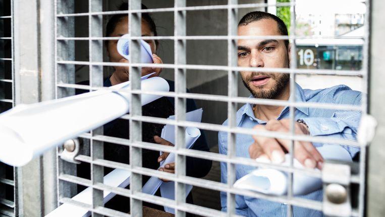 Medewerkers van denk reiken via het hek van het partijkantoor in Rotterdam de persverklaring aan. Beeld Freek van den Bergh