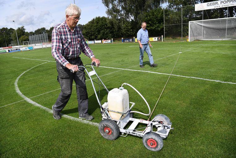 Fons Lammerink trekt de lijnen op het veld van VV Reutum.  Beeld Marcel van den Bergh / de Volkskrant