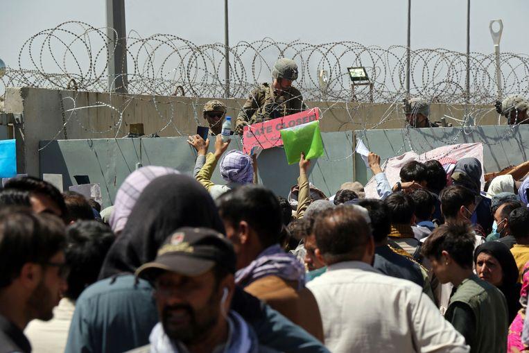 Een Amerikaanse militair houdt een bord vast waarop staat dat de poort naar het internationale vliegveld van Kaboel is gesloten. Beeld AP
