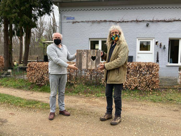 Bart Staal (links) overhandigt het deurtje aan Jo Lommelen (rechts) van de dienst erfgoed – Kamer voor Heemkunde.