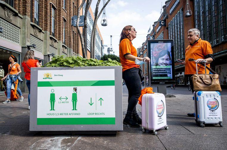 Werknemers uit de reisbranche lopen met rolkoffers door het centrum van Den Haag om aandacht te vragen voor de benarde situatie van de branche.  Beeld ANP
