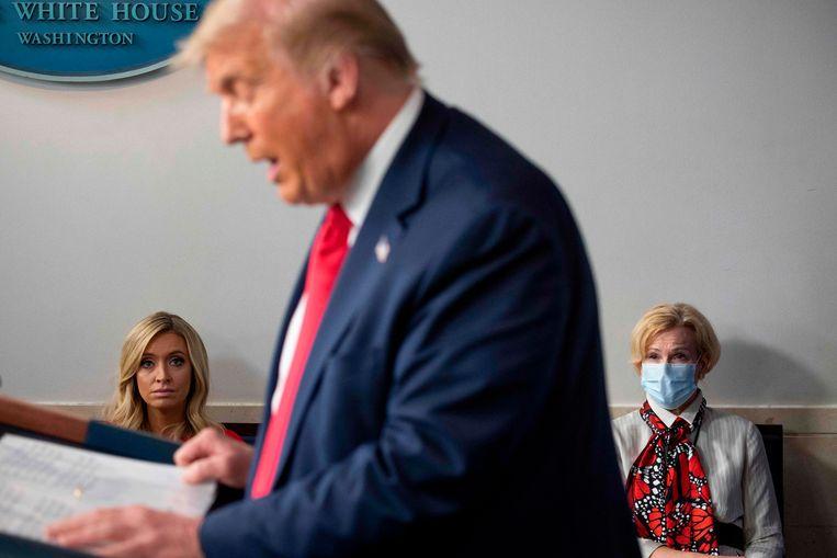 Dr. Deborah Birx (rechts, met mondmasker) en de woordvoerder van Trump luisteren eind juli naar een persconferentie van de Amerikaanse president.  Beeld AFP
