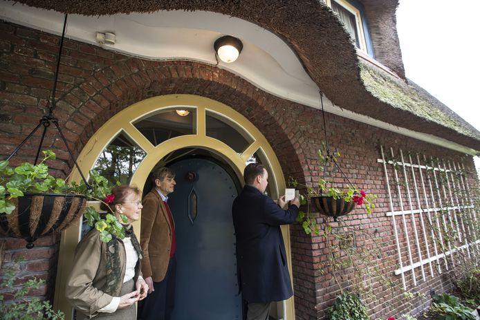 Wethouder Diepemaat bevestigt het monumentenbordje bij de voordeur van villa De Keizer, onder het toeziend oog van de bewoners, het echtpaar Gaymans.