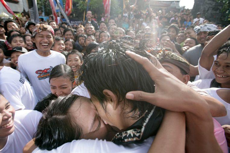 Een innige kus op het 'Kussenfestival' in Sesetan op Bali. Het kussen helpt het dorp beschermen tegen het ongeluk. Beeld Getty Images