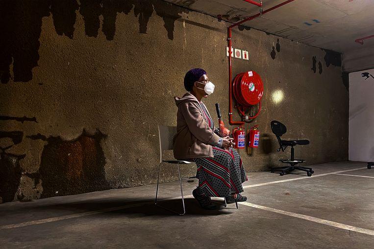 Een vrouw wacht in een parkeergarage in Johannesburg op een coronatest.  Beeld AP