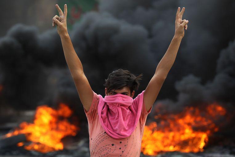 Een demonstrant maakt het vredesteken in Bagdad.