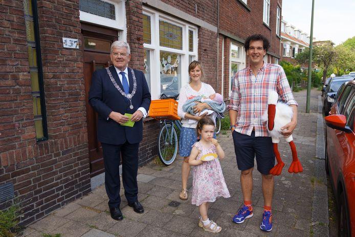 Burgemeester Jan van Zanen bezoekt de 550.000ste inwoner van Den Haag. Het is de op 1 juni geboren Nanke Verschoor, hier in de armen van haar moeder Wabke.  Vader Jerke (r.) en dochter Klaske (op de voorgrond) completeren het gezin.