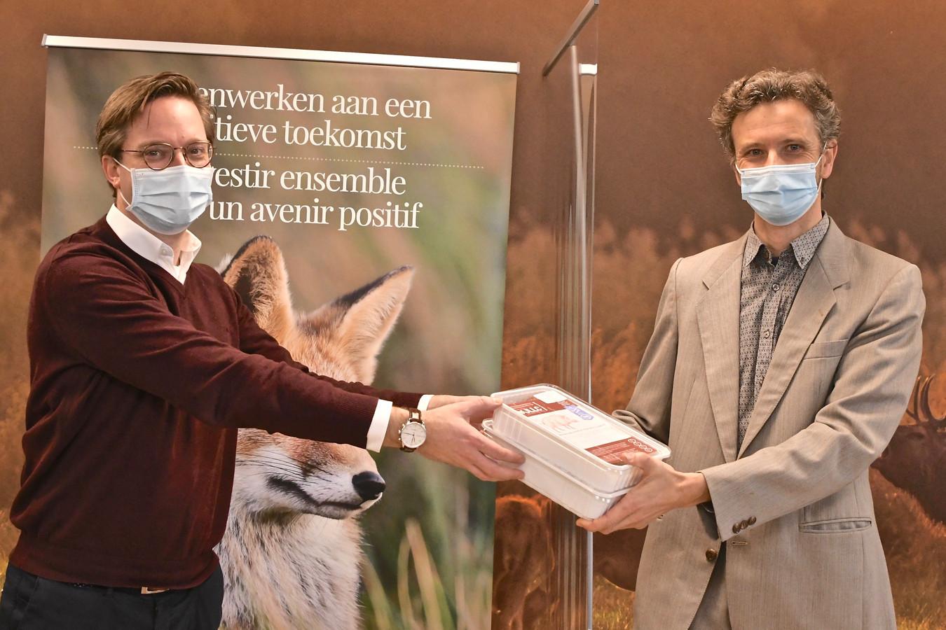Lysander Werbrouck van JLLC overhandigt enkele wildburgers aan de coördinator van de Voedselbanken.