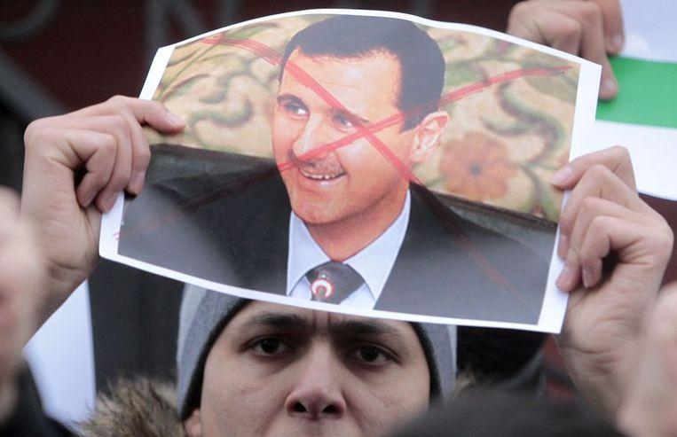 Een Syrische demonstrant houdt een afbeelding van president Assad met een kruis omhoog. Beeld reuters