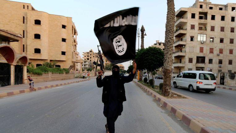 Een lid van ISIS (Islamitische Staat in Irak en groot-Syrië) zwaait met de vlag van ISIS in Raqqa. Beeld REUTERS
