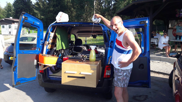 Rien Linthout bij zijn bestelbusje dat is omgebouwd tot mini-camper.