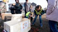 Leerlingen De Knipoog steken teletijdscapsule met tegels onder de grond
