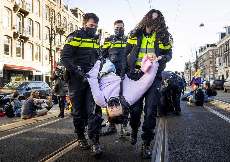 Rebelerende demonstrant wordt afgevoerd vanaf de Overoom in Amsterdam. Beeld EPA