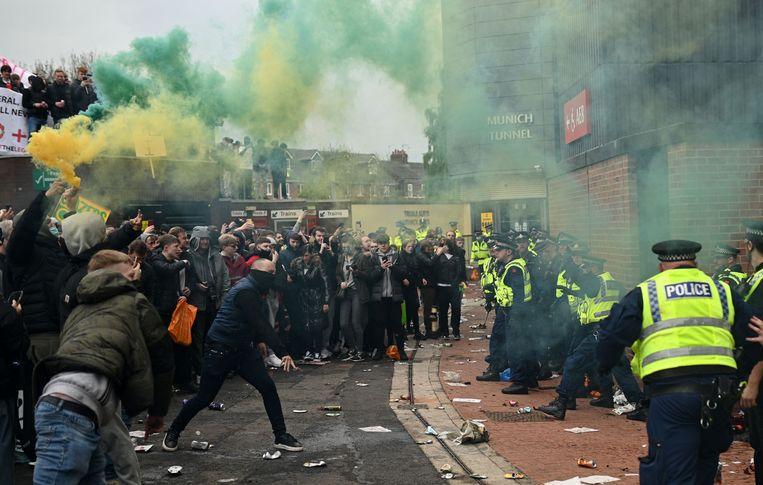 De politie probeert de fans uit het stadion te houden, maar slaagt daar niet in. Beeld AFP