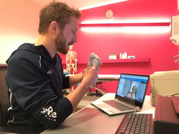 Fysiotherapeut Benjamin Langman geeft via beeld-bellen uitleg aan een patiënt.