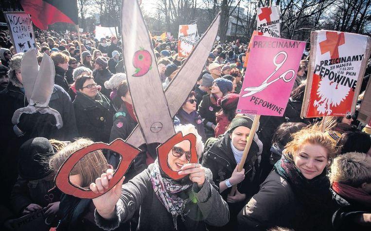 Feministes demonstreren in Warschau ter ere van Internationale Vrouwendag met de leuze 'knip het koord door' tussen kerk en staat. Beeld afp