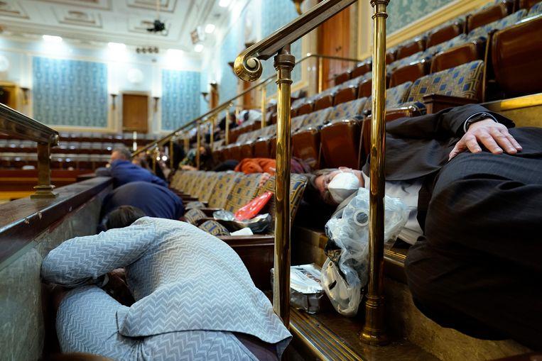 Mensen houden zich schuil in de galerij van het Huis van Afgevaardigden. Beeld AP