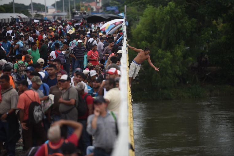 Hondurese migranten springen in de rivier Suchiate, die Mexico en Guatemala van elkaar scheidt. Beeld EPA