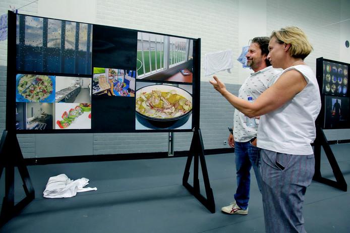 Twee medewerkers van de gevangenis bekijken de expositie van de gevangenen.
