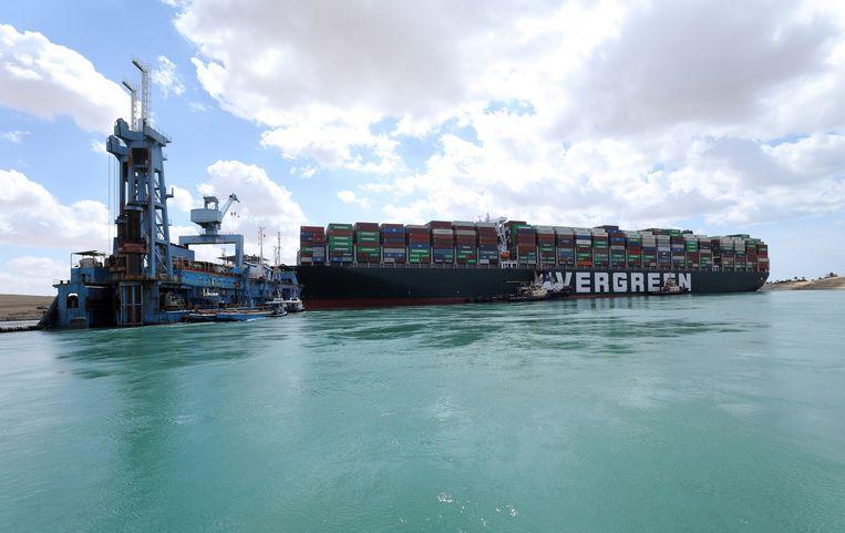 Baggermateriaal werkt samen met sleepboten eraan om de vastgelopen Ever Given vlot te trekken.  Beeld EPA