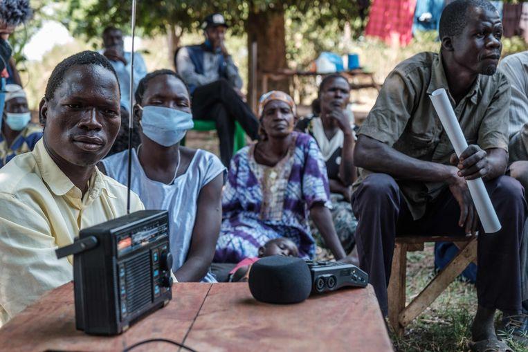 Mohammed Olanyia (L) die zijn hele familie verloor in de Lukodi massacre, luistert naar de radio op het moment dat het vonnis tegen Dominic Ongwen wordt uitgesproken bij het ICC in Den Haag.  Beeld AFP
