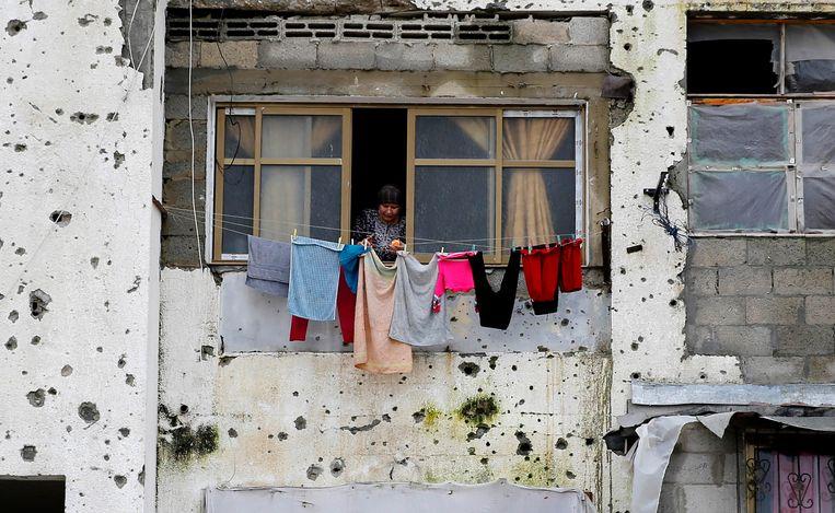 Een vrouw hangt de was op bij een appartementencomplex in Gaza-stad, dat beschadigd is geraakt tijdens de oorlog tussen Israël en Hamas in 2014.  Beeld AP