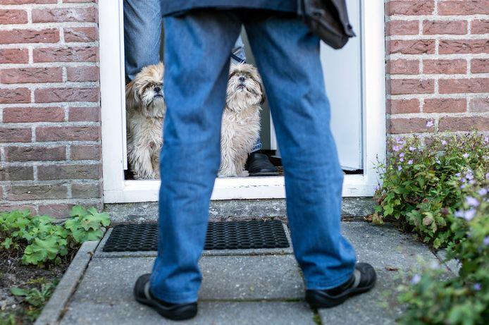 De hondencontroleur aan de deur. Voor Diksie en Vlekje was alles in orde. Hun baas betaalt keurig belasting.