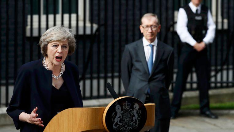 Theresa May geeft haar eerste speech als premier, met op de achtergrond haar echtgenoot Philip. Beeld REUTERS