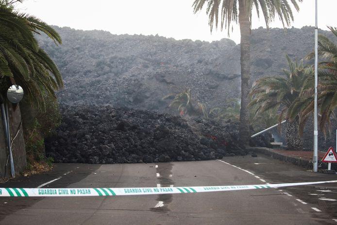 De Spaanse autoriteiten hebben een weg afgezet die is geblokkeerd door de gigantische lavastroom uit de vulkaan Cumbre Vieja.