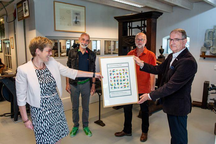 Burgemeester De Vries (links) neemt de nieuwe Koppermaandagprent in ontvangst. Naast haar staan van links naar rechts Joost Klinkenberg, die de prent ontwierp, Cees Jochems (secretaris) en Frans de Nijs (voorzitter van het Nederlands Drukkerij Museum.)
