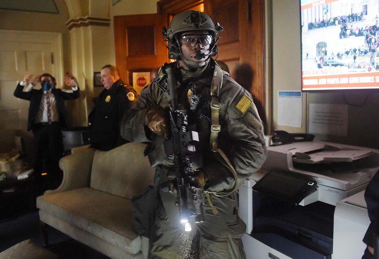 Stafleden houden hun handen omhoog als een lid van de Capitool-politie onderzoekt of de Trump-supporters, die kort daarvoor het Capitool zijn binnengedrongen, zich nog buiten de ruimte bevinden.  Beeld AFP