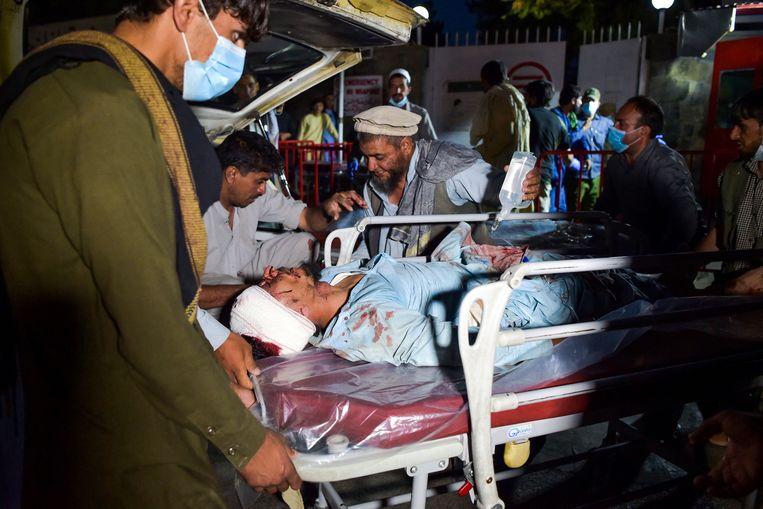 Een gewonde man wordt weggevoerd na de explosies in Kaboel. Het is nog onduidelijk hoeveel slachtoffers er zijn gevallen. Beeld al