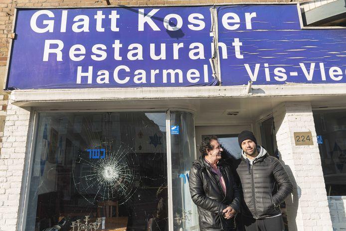 Eigenaar Daniel Baron (R) staat met zijn vader voor het Israëlische restaurant HaCarmel en laat de schade aan zijn restaurant zien.