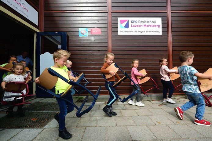 Leerlingen van basisschool Lavoor in Roosendaal dragen hun stoeltjes naar buiten, want ze krijgen nieuw schoolmeubilair