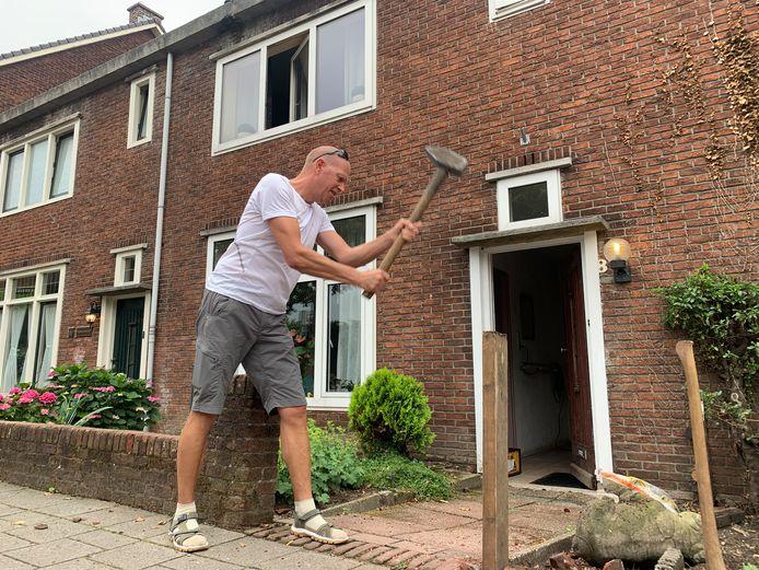 Gert Jan de Mare slaat een paal de grond in, met de bedoeling om daar een vloedschot tegenaan te zetten voor als er weer een hoosbui komt.