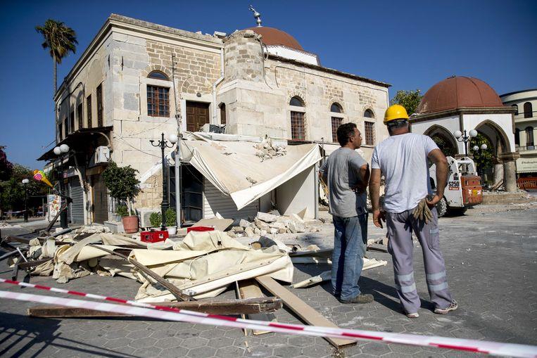 Puinruimers ruimen de schade op die is ontstaan door de aardbeving op het Griekse eiland Kos. Beeld ANP