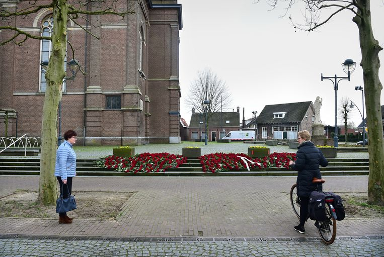 In Erp, waar zeven doden vielen, hebben bewoners bij de Sint-Servatiuskerk meer dan duizend rode rozen gelegd. Bewoners praten met elkaar op grote afstand.  Beeld null