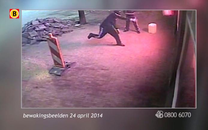 Still uit bewakingsbeelden: twee mannen smijten met stoeptegels een ruit van SanSoleil in. Daarna stichten ze binnen brand.