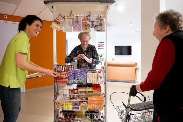 Bewoonsters Jeanne en Clara kopen iets bij de winkelkar van Carla.