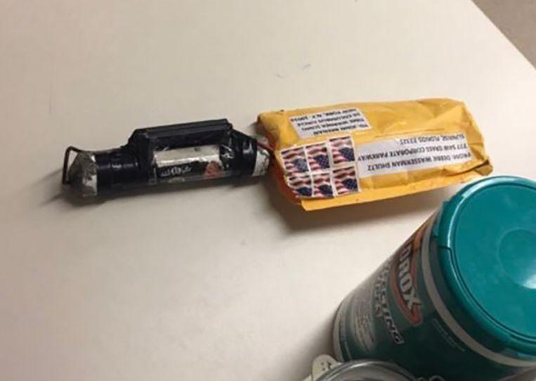 Alle bommen zagen er ongeveer hetzelfde uit: een gele envelop met daarin een ijzeren buis van ongeveer 15 centimeter. Dit is de envelop die bij CNN werd bezorgd. Op de buis is de sticker met de nepvlag te zien. Beeld AFP
