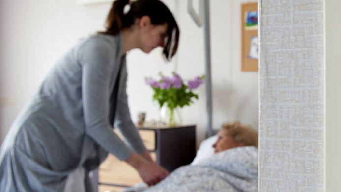 Een bedlegerige vrouw in een aanleunwoning krijgt hulp aan huis.