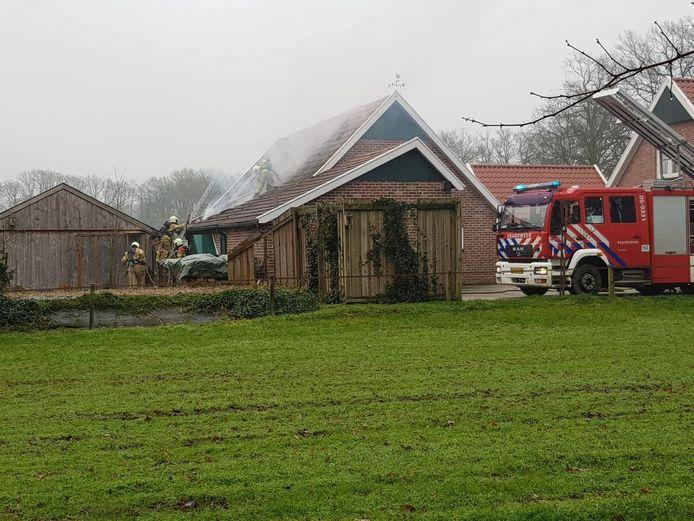 De brandweer is druk met het blussen van de brand in de paardenschuur in Winterswijk.